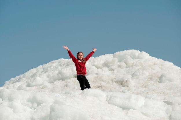 Fille debout sur un tas de neige à winnipeg beach, manitoba, canada