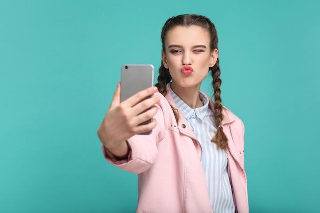 Fille debout tenant un téléphone intelligent mobile et faisant un selfie ou un appel vidéo avec un baiser