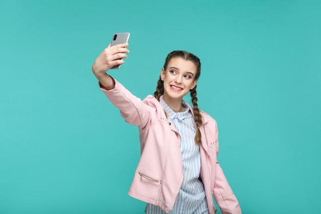 Fille debout tenant un téléphone intelligent mobile et faisant un selfie avec un sourire à pleines dents