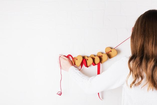 Une fille décore une salle avec des cookies en forme de coeur sur un mur blanc. symbole d'amour chaleureux et fond de saint valentin et concept d'anniversaire festif