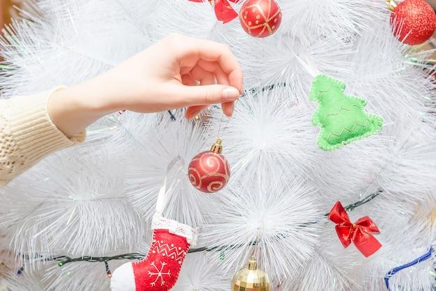 Fille décore le sapin de noël blanc créatif avec une boule rouge. se préparer pour le nouvel an et les vacances de noël