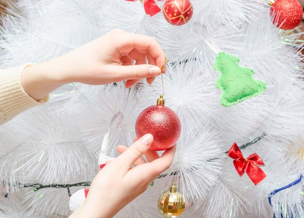 Fille décore le sapin de noël blanc créatif avec une boule rouge.