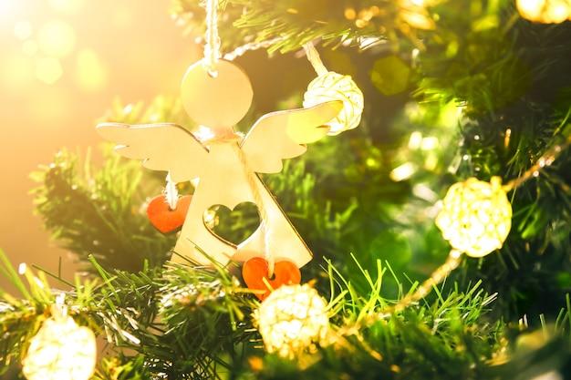 La fille décore le sapin de noël avec des lumières. ange blanc avec jouet coeurs dans les mains de la femme. concept d'amour et de vacances. ambiance du nouvel an. style hygge. temps magique.