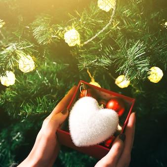 La fille décore le sapin de noël avec des lumières. boîte présente avec des jouets dans les mains de la femme. coeur moelleux blanc. concept d'amour et de vacances. ambiance du nouvel an. style hygge. temps magique.
