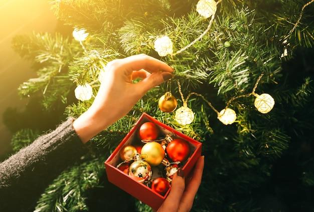 La fille décore le sapin de noël avec des lumières. boîte présente avec des jouets dans les mains de la femme. concept d'amour et de vacances. ambiance du nouvel an. style hygge. temps magique.