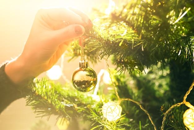 La fille décore le sapin de noël avec des lumières. jouet boule d'or dans les mains de la femme. concept d'amour et de vacances. ambiance du nouvel an. style hygge. temps magique.
