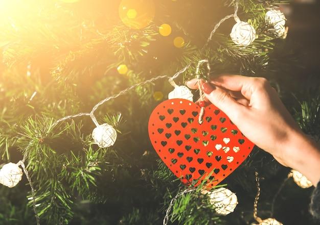 La fille décore le sapin de noël avec des lumières. jouet coeur rouge dans les mains de la femme. concept d'amour et de vacances. ambiance du nouvel an. style hygge. temps magique.