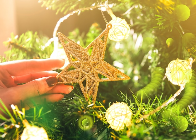 La fille décore le sapin de noël avec des lumières. jouet étoile dorée dans les mains de la femme. concept d'amour et de vacances. ambiance du nouvel an. style hygge. temps magique.