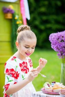 Fille décorer des petits gâteaux dans la cour
