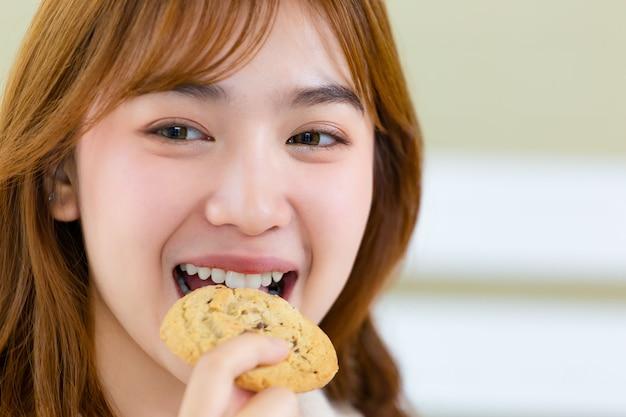 La fille et déguste de délicieux biscuits gastronomiques