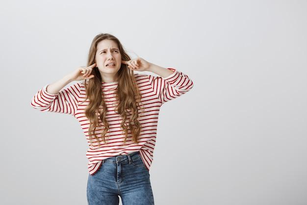 Une fille dérangée et agacée ferme les oreilles et regarde le coin supérieur droit, se plaignant de voisins bruyants
