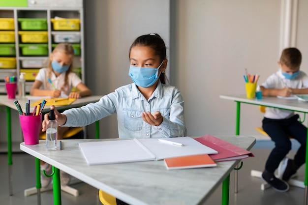 Fille désinfectant dans la salle de classe