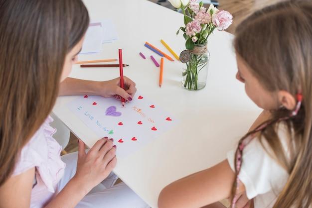 Fille dessinant des coeurs sur papier