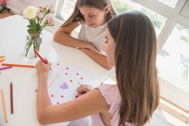Fille dessinant des coeurs rouges sur papier