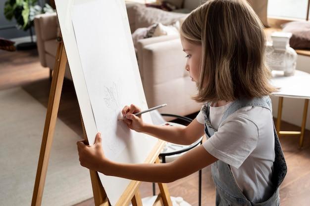Fille dessinant à la maison coup moyen