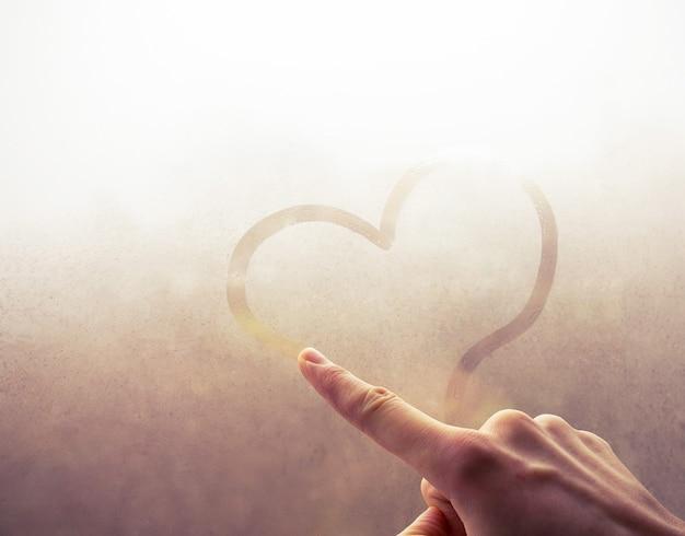 Fille dessine un coeur sur fond abstrait verre brumeux