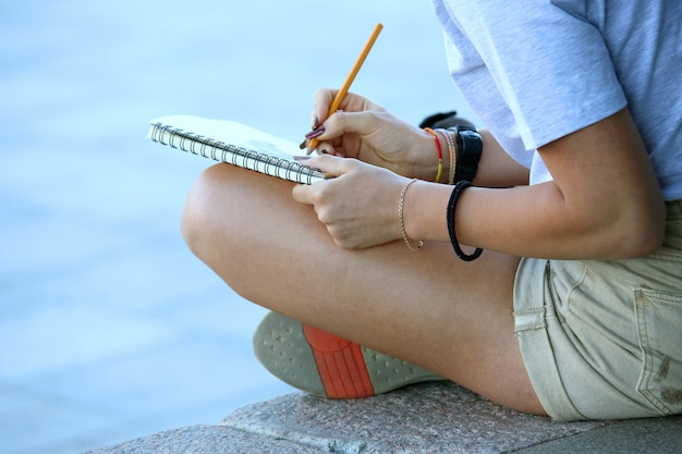 Fille dessine dans un cahier assis sur le trottoir