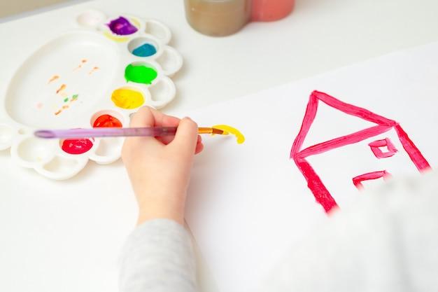 La fille dessine la maison et le soleil.