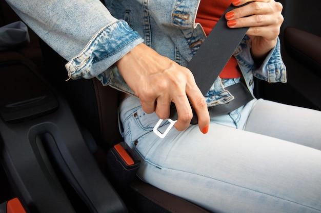 La fille détache la ceinture de sécurité dans la voiture.