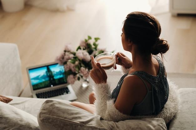 Une fille détendue à la maison boit du café et regarde un film calme domestique la fille est assise confortablement sur le canapé et boit du café.