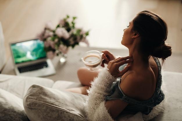 Fille détendue à la maison buvant du café. paix intérieure. la fille est assise confortablement sur le canapé et boit du café