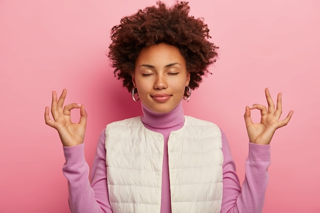 Une fille détendue à la peau sombre étant patiente et soulagée, montre un geste mudra zen, pratique le yoga après le travail, vêtue d'un gilet blanc, se tient les yeux fermés sur fond rose.