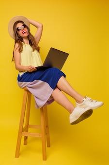Fille détendue portant une robe d'été lumineux travaillant avec un ordinateur portable assis sur la chaise sur un mur isolé
