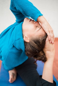 Fille détendue, pratiquant le yoga à la maison