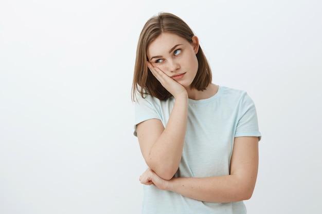 Fille déteste assister à des cours ennuyeux à l'université, le visage appuyé sur la main, roulant les yeux de l'ennui et de l'ennui debout indifférent et mécontent sur le mur gris en t-shirt à la mode