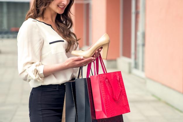 Une fille détient une excellente chaussure blanche et des sacs en papier. espace copie