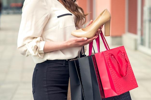 Une fille détient une excellente chaussure blanche et des sacs en papier. fermer.