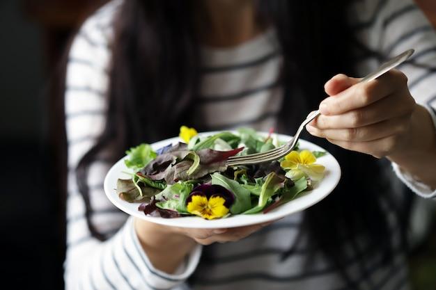 Fille détient une salade fraîche avec des violettes sur une plaque.