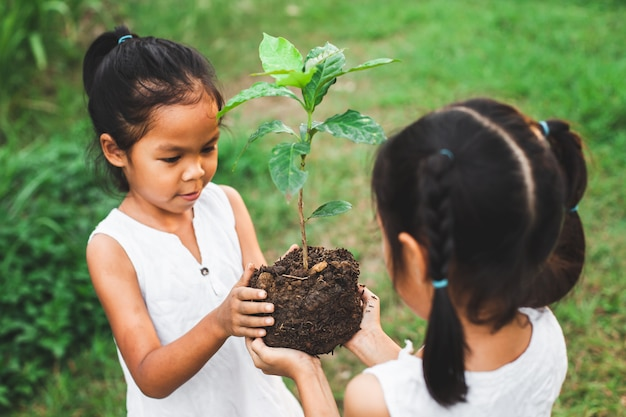 Fille de deux enfants tenant le jeune arbre pour la plantation ensemble comme concept de sauver le monde