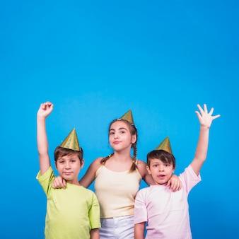 Fille et deux garçons avec bras levés sur fond bleu