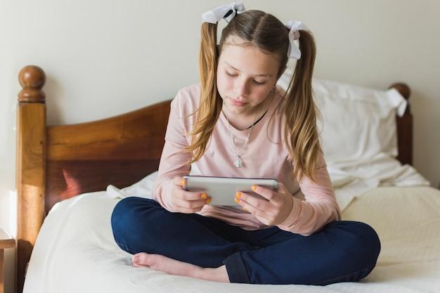 Fille avec deux queues de cheval assis sur un lit en regardant un téléphone portable