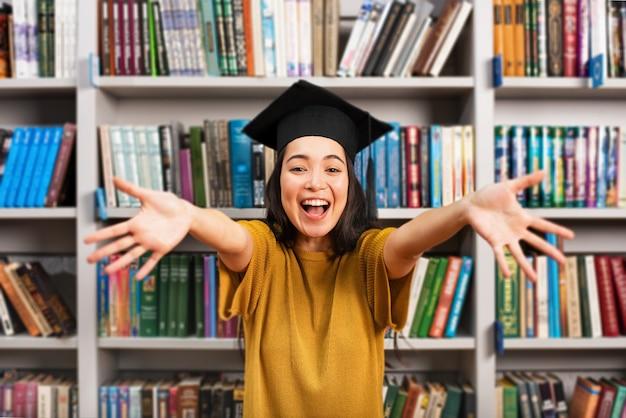 Fille diplômée devant une bibliothèque