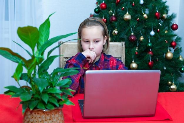La fille discute sur l'ordinateur portable à l'arrière-plan de l'arbre de noël