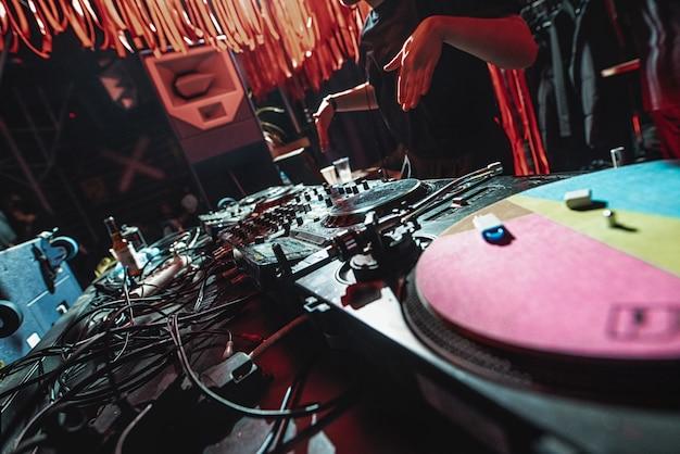 La fille dj joue avec des joueurs d et une console de mixage