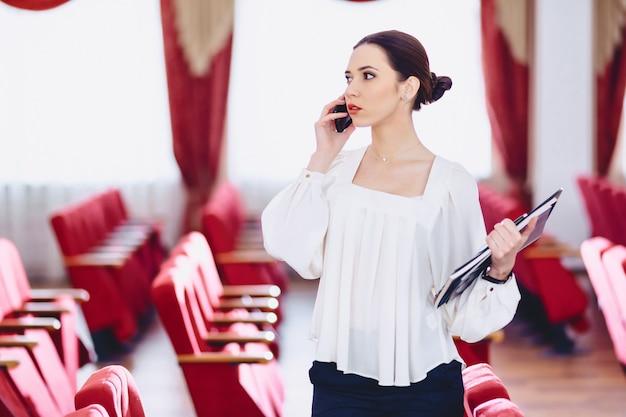 Fille avec documents parle par téléphone