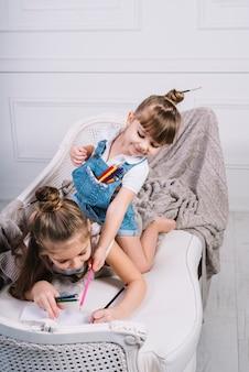Fille donnant un crayon à une autre fille sur un canapé