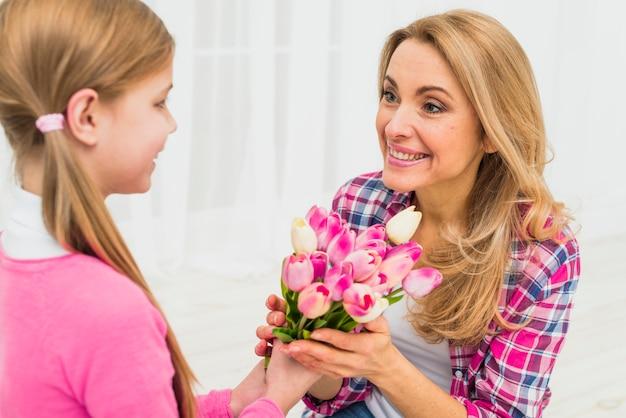 Fille donnant des fleurs de tulipes à la mère