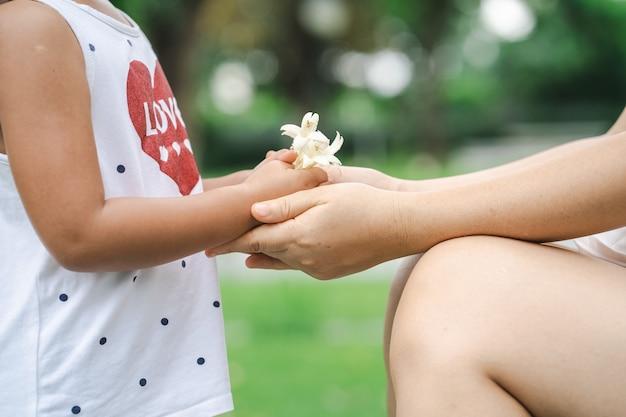 Fille donnant à sa mère un bouquet de fleurs blanches au jardin