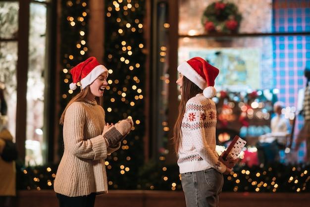 La fille donne un cadeau à son amie dans la rue. portrait de jeunes amis mignons heureux