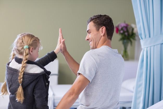 Une fille donne un high five à son père malade