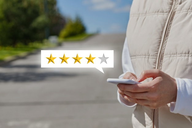 Une fille donne une note parmi les étoiles et une critique dans un smartphone marchant dans la rue.