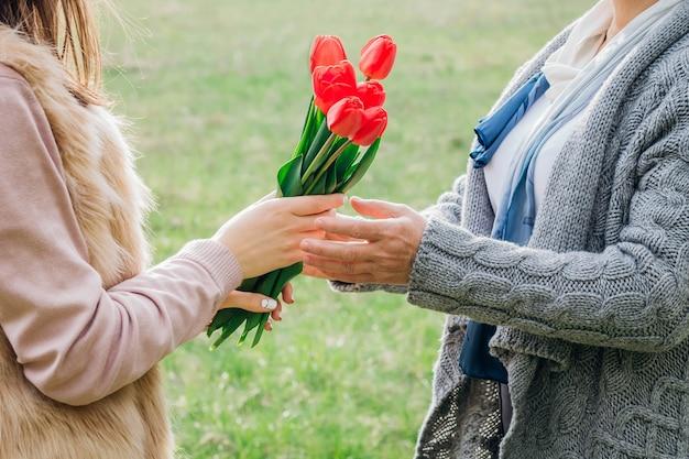 Fille donne à sa mère des tulipes rouges