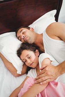 Fille dormant à côté de son père sur le lit à la maison
