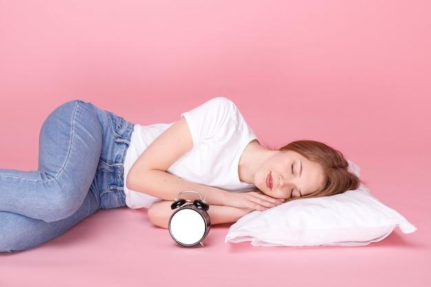 Fille dort sur l'oreiller à côté du réveil sur fond rose