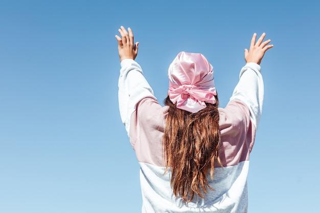 Fille avec le dos tourné avec un foulard rose. journée internationale du cancer du sein, avec le ciel en arrière-plan.