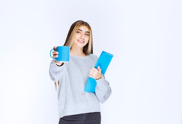Fille avec un dossier bleu partageant une tasse de café avec son collègue.